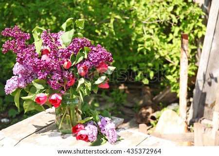 Beautiful fresh bouquet of violet lilac and red tulips