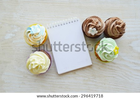 beautiful, fresh, delicious cupcakes decorated with cream, with an empty notepad for notes on a wooden table - stock photo