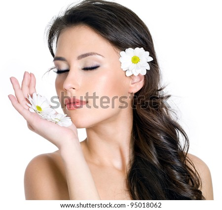 Beautiful fresh face of young woman with flowers - white background