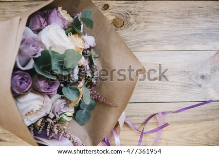 Beautiful fresh flower bouquet with eucalyptus,roses and english roses packed in craft paper on the old wooden table background