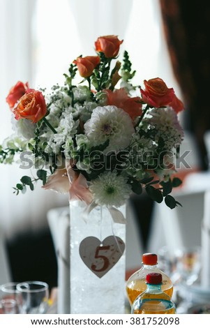 Beautiful fresh flowers bouquet centerpiece at wedding reception table - stock photo