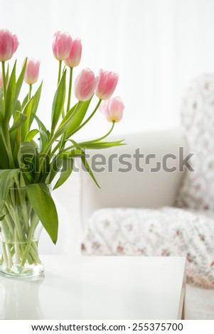 Beautiful fresh flowers in a vase on a table - stock photo