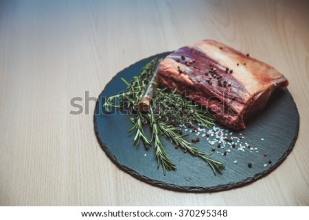 Beautiful fresh meat with rosemary and spices on the Board - stock photo