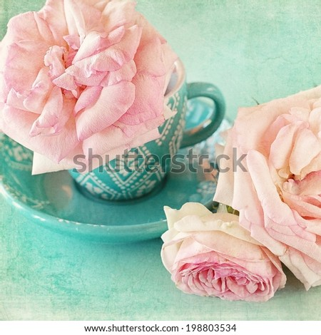 Beautiful fresh pink roses in a cup  on a blue background . - stock photo