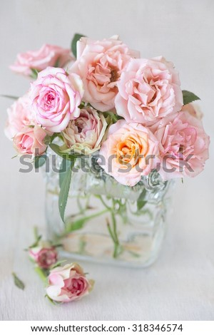 Beautiful fresh pink roses in a vase on a table .light background. - stock photo