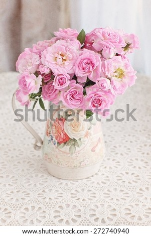 Beautiful fresh pink roses on a table. light background. - stock photo