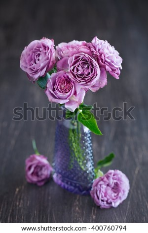 Beautiful fresh purple roses in a vase on a dark brown wooden background . - stock photo