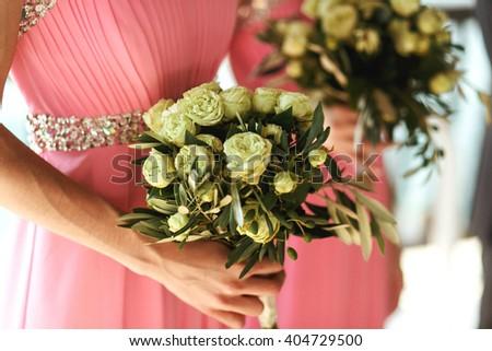 Beautiful fresh roses in wedding bouquet in bridesmaids hands closeup - stock photo