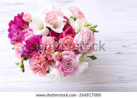 Beautiful fresh spring flowers on wooden table, top view - stock photo