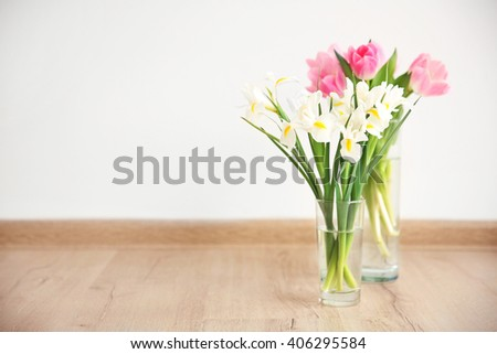 Beautiful fresh tulips and irises on wooden floor against white wall background