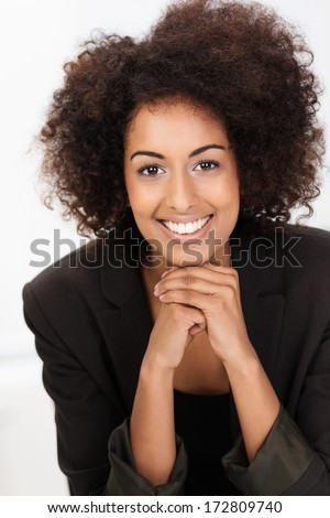 Beautiful friendly African American businesswoman with a frizzy afro hairstyle sitting with her chin on her hands smiling at the camera, closeup portrait - stock photo