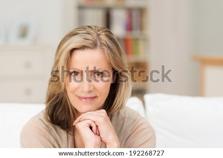 Beautiful friendly middle-aged woman sitting looking directly at the camera with a smile and her chin resting on her clasped hands