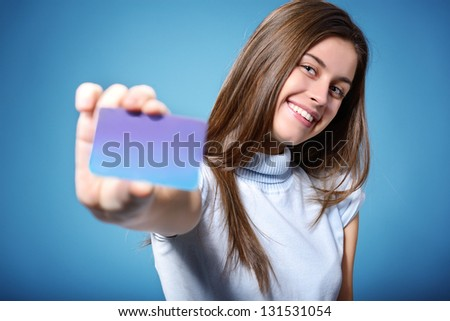 beautiful friendly smiling confident teen girl showing card in hand, over blue background - stock photo