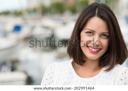 Beautiful friendly young woman with shoulder length brown hair posing outdoors looking directly at the camera with a gentle smile - stock photo
