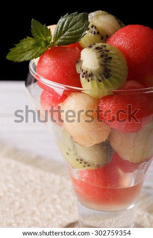Beautiful fruit salad of watermelon, melons and kiwi fruit in a glass close up vertical