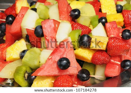 Beautiful fruit salad pieces on wooden chopsticks - stock photo