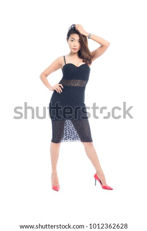 Beautiful full body Asian woman posing in sexy slinky black lace dress isolated on a white background.