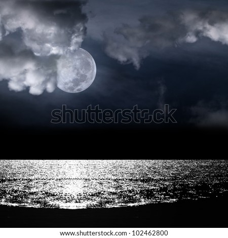 Beautiful full moon behind fantasy cloudy sky over water with reflection - stock photo
