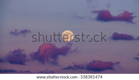 Beautiful full moon scene with a purple sky and clouds at dusk out in the country - stock photo