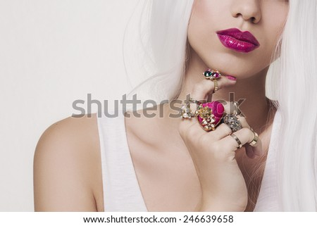 Beautiful full pink lipstick with jewelry on fingers and white hair - stock photo