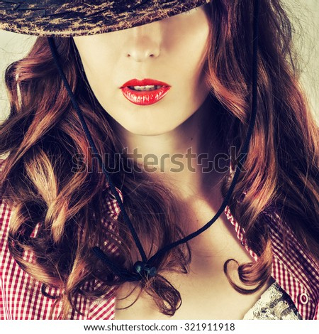 Beautiful full red lips. Part of face of young beautiful woman covered by cowboy hat - stock photo