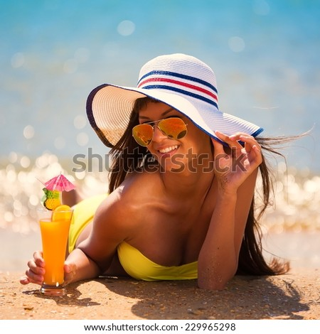beautiful fun and joy brunette smiling woman in yellow bikini and white hat drink orange cocktail in  tropical  blue sea water has sports and tan body - stock photo