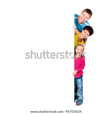 Beautiful fun family behind a white blank - stock photo