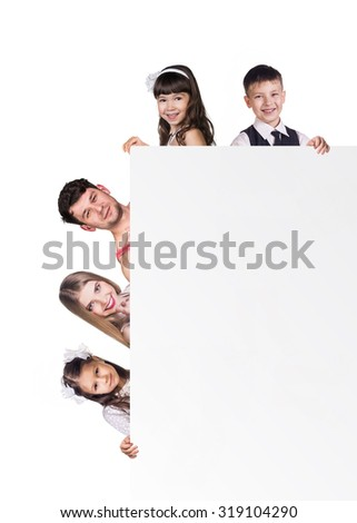 Beautiful fun family behind a white placard on the white background