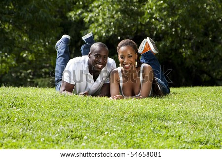 Beautiful fun happy smiling laughing African American couple laying on grass in park, wearing white shirts and blue jeans.