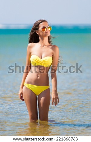 beautiful fun joy sexy smiling brunette lady woman yellow bikini sunglasses tropical blue sea water Mauritius has sports and tan body cream adventure sunscreen close up sunbathing leisure amazing
