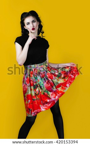 Beautiful fun summer girl with pretty teeth smile in pinup style in big heat, flower skirt and unusual pose. Emotional colorful warm comic excited retro spring style woman on orange background. - stock photo