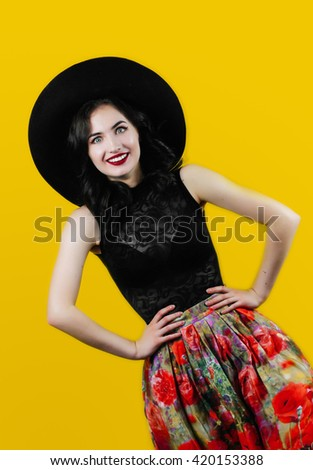 Beautiful fun summer girl with pretty teeth smile in pinup style in vinyl style hat, flower skirt and unusual pose. Emotional colorful warm comic excited retro spring style woman on orange background. - stock photo