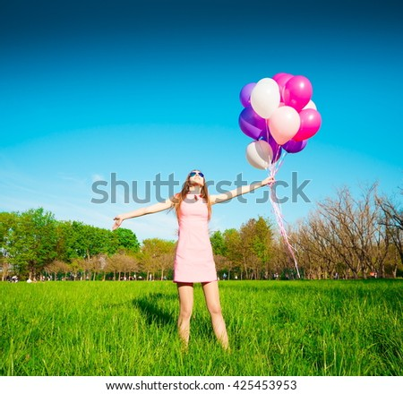 Beautiful fun woman holding multicolored helium balloons. Has smiling face, long hair and legs, clothed pink dress, sunglasses. Has slim body. Portrait nature green forest. Sunny day and blue sky.