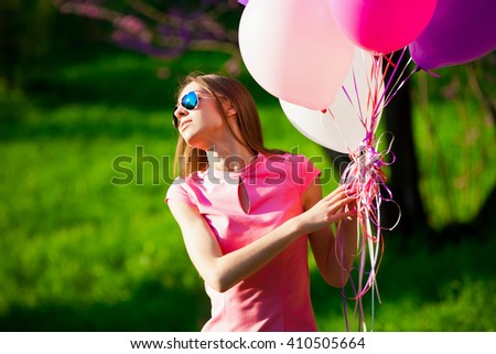 Beautiful fun woman holding multicolored helium balloons. Has smiling face, long hair, clothed pink dress, sunglasses. Has slim body. Portrait in green forest. Sunny day and blue sky. Close up - stock photo