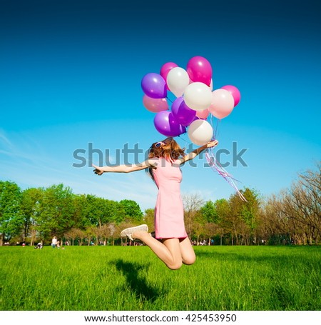 Beautiful fun woman jumping with helium balloons. Has smiling face, long hair and legs, clothed pink dress, sunglasses. Has slim body. Portrait in city park. Sunny day and blue sky. - stock photo