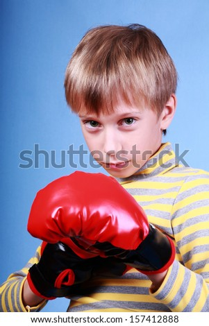 Beautiful funny blond boy wearing red boxer gloves looking dangerous