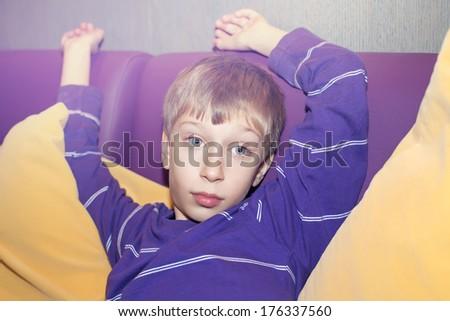 Beautiful funny boy sitting on a purple sofa looking bored and sleepy - stock photo