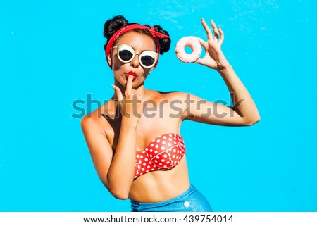 Beautiful, funny, cheerful,  tanned girl eats a sweet donut glaze, licks his fingers, dressed in a bright bikini, sunglasses, hairstyle with horns, makeup, lovely emotions, blue wall, perfect body - stock photo