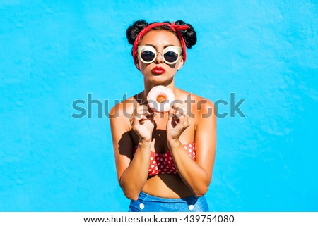 Beautiful, funny, cheerful, tanned hipster girl eats a sweet donut glaze, wearing a bright top and shorts, sunglasses, hairstyle with horns, makeup, crazy emotions, cute blowing lips, blue wall - stock photo