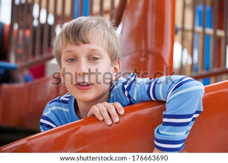 Beautiful funny child playing on playground in summer sliding