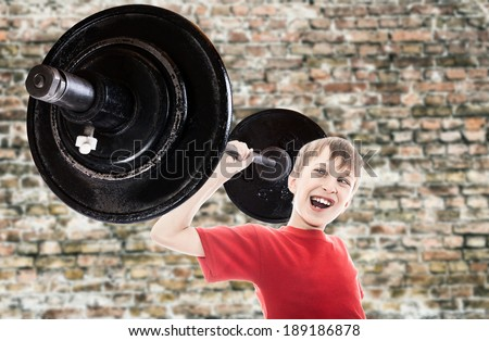 Beautiful funny child superhero lifting very big weight  with funny expression (child success concept)  - stock photo