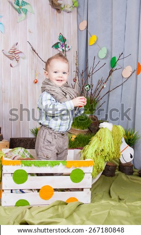 Beautiful funny little boy playing among easter spring scenery. Studio filming a child in a bright, juicy spring location. Child is happy and cheerful. - stock photo
