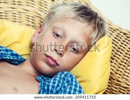Beautiful funny little child lying on cozy wicker sofa looking sad and sick. Closeup portrait. - stock photo