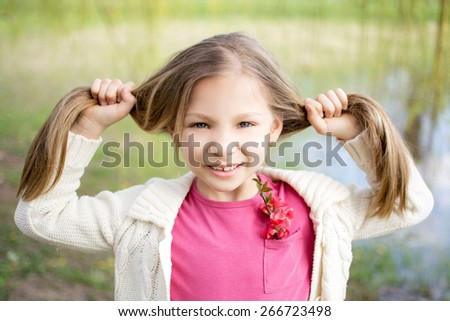 Beautiful funny little girl in the park at spring. - stock photo