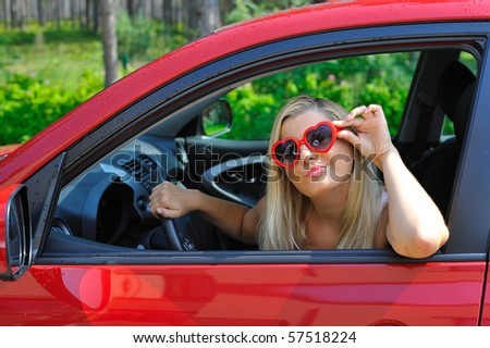 beautiful funny woman in heart shaped glasses in red shiny car outdoors - stock photo