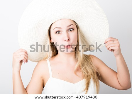 beautiful funny young blonde woman in white tank top and a large white hat smiling and poses faces - stock photo
