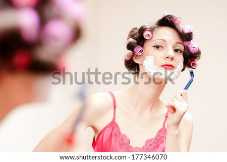 Beautiful funny young woman shaving with foam & razor her face - stock photo