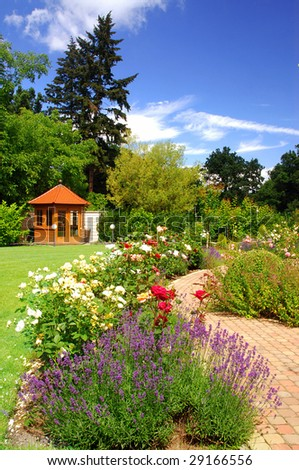 Beautiful garden with blooming roses, brick path and a small gazebo - stock photo