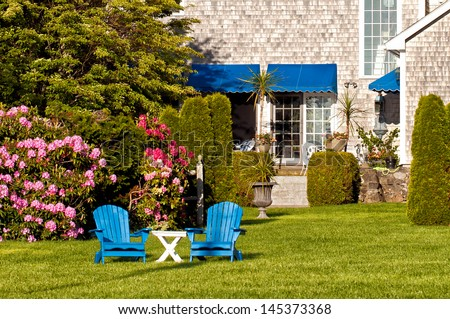 Beautiful garden with outdoor furniture - stock photo