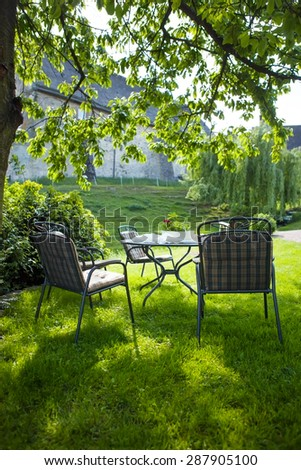 beautiful garden with white table and chair - stock photo